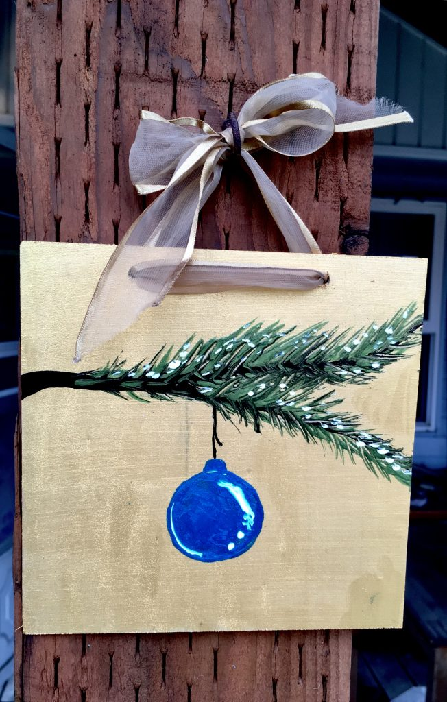 pine branch painting with blue glass ball hanging on a front porch post